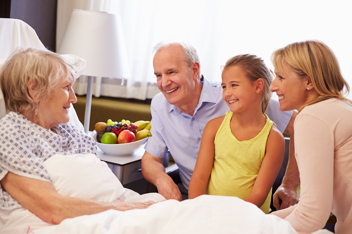 A family speaks with a patient in a skilled nursing facility