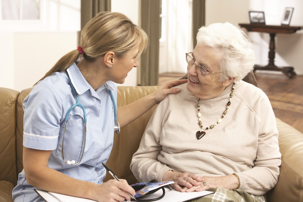 A caregiver works with a patient in her home to provide home health care