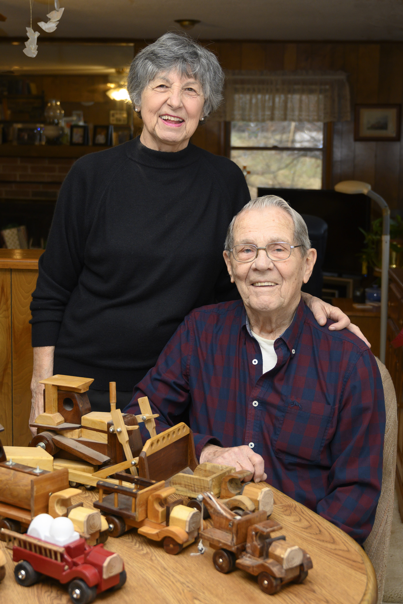 Carl and his wife, Vonnie, with his wooden toy trucks