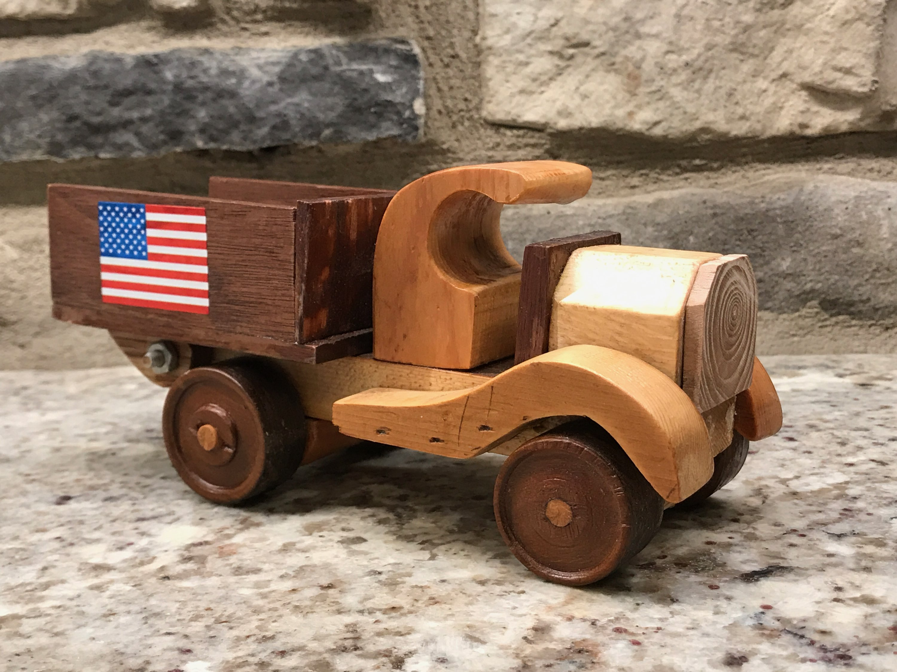 A handmade wooden toy truck with the American flag