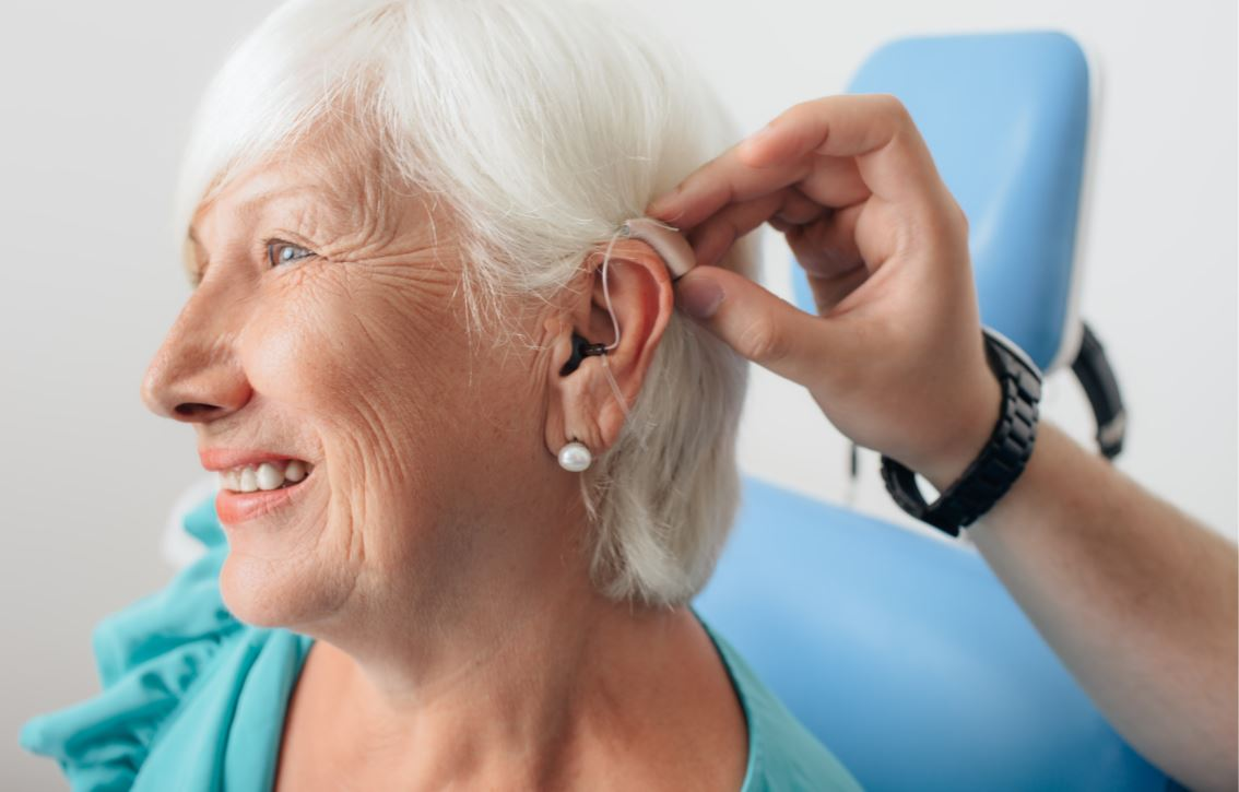 Clinician placing hearing aid on woman's ear