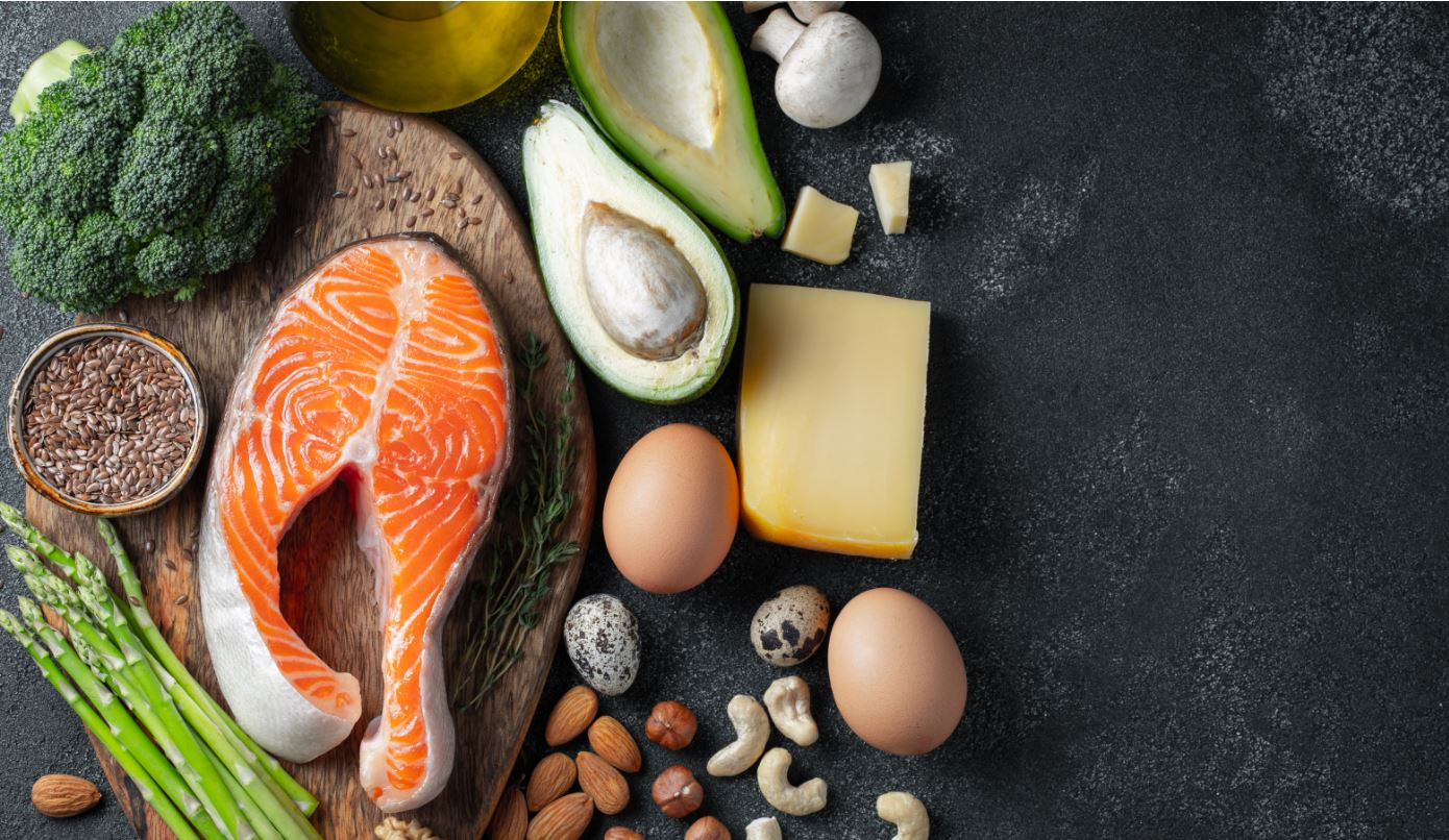 Image of foods that give omega-3's such as fish, avacado, nuts, eggs, oil, and seeds on a cutting board on a black chalkboard background