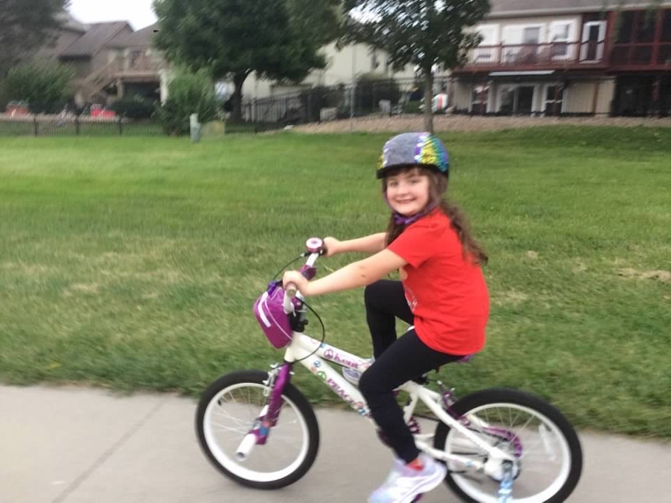 Amelia loves bike riding. One day, she will achieve her goal of riding without the training wheels!