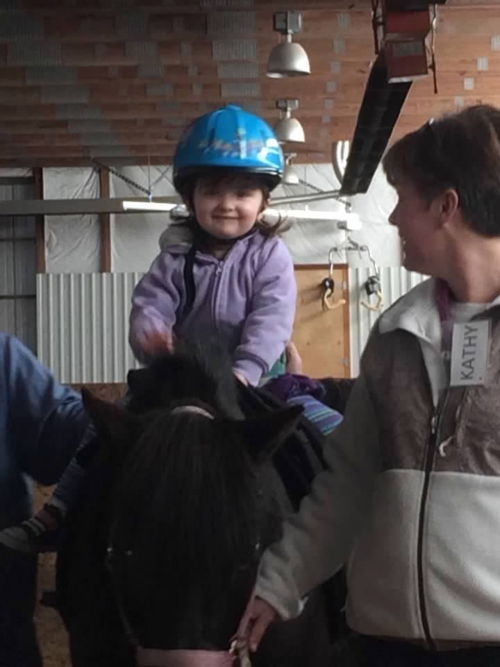 Amelia at her first hippotherapy lesson on a horse.