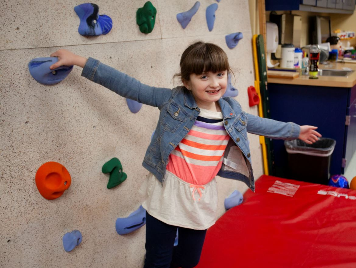 Amelia, a patient Saint Luke's The Children's SPOT, standing by the climbing wall