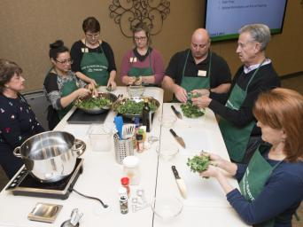 A Food as Medicine Everyday program class gathers around a table.