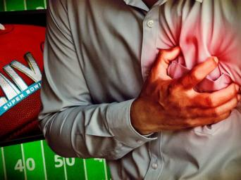 Man grabbing his heart next to LIV Super Bowl football