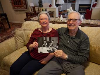The Zollar's, Bishop Spencer Place residents, sitting on their couch, holding a black and white photo from when they were a younger couple