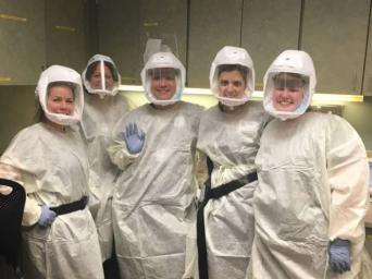 Nurses standing together wearing PPE
