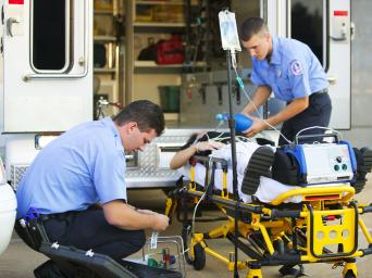 Two first responders treating a patient by an ambulance