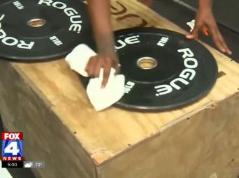 FOX4 News. Hand cleaning off weights with a rag