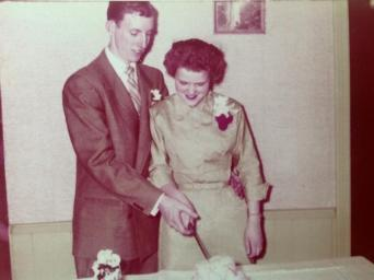Jim and Rosie cutting cake at their wedding.