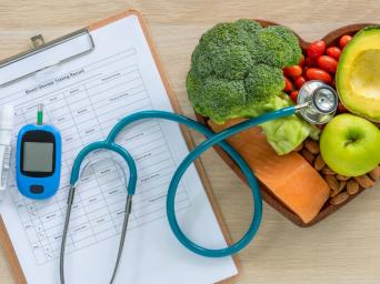 blood glucose testing paper with a stethoscope and a heart shape bowl with healthy foods to fight diabetes